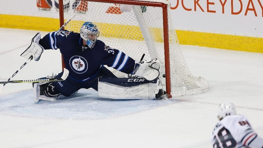 Winnipeg Jets goalie Connor Hellebuyck (37) can't stop a goal from Chicago Blackhawks right wing Patrick Kane (88) during the first period of an NHL hockey game Friday, Feb. 10, 2017, in Winnipeg, Manitoba. (John Woods/The Canadian Press via AP)