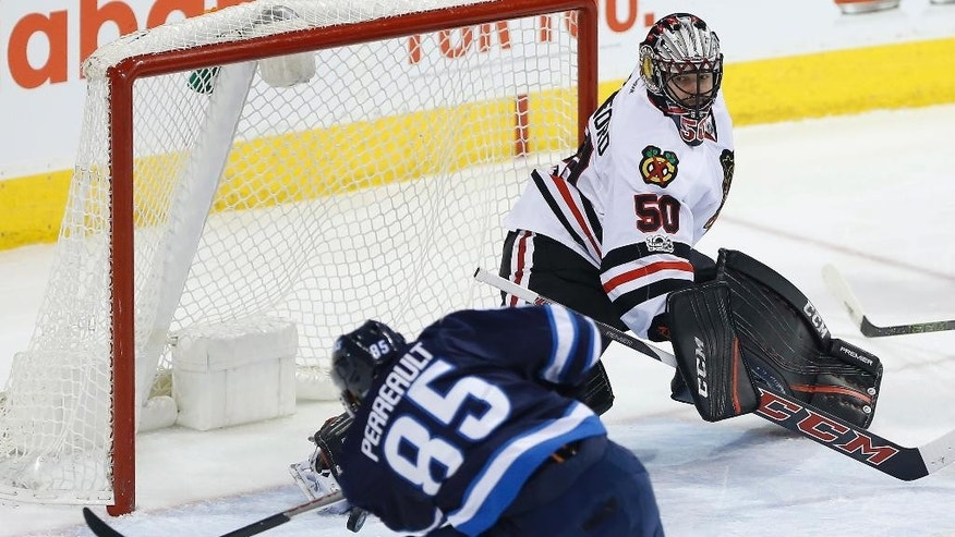 Winnipeg Jets center Mathieu Perreault (85) misses the open net against Chicago Blackhawks goalie Corey Crawford (50) during the first period of an NHL hockey game Friday, Feb. 10, 2017, in Winnipeg, Manitoba. (John Woods/The Canadian Press via AP)