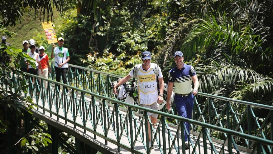 Danny Willet of England, right, talks to his caddie on the second hole during the second day of the Maybank Championship golf tournament in Kuala Lumpur, Malaysia , Friday, Feb. 10, 2017. (AP Photo/Vincent Thian)