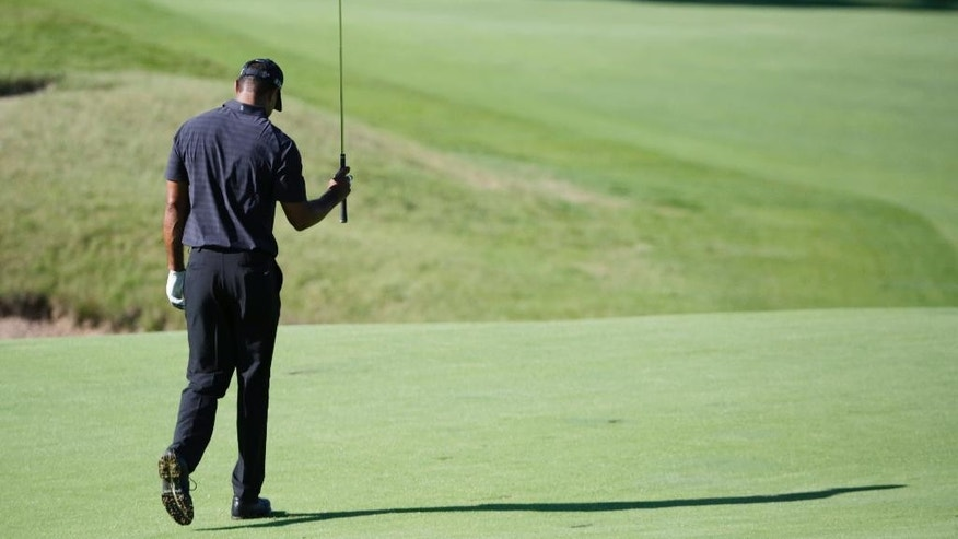 FILE - In this Aug. 12 2015, file photo, Tiger Woods reacts after his approach shot on the 18th hole during a practice round for the PGA Championship golf tournament at Whistling Straits in Haven, Wisc. Woods pulled out of his next two tournaments because of ongoing back problems, a somber outlook for a 14-time major champion whose comeback barely lasted three tournaments before another setback. Woods said Friday, Feb. 10, 2017, on his website that he was still coping with back spasms that he attributed to his withdrawal from the Dubai Desert Classic last week. (AP Photo/Brynn Anderson, File)