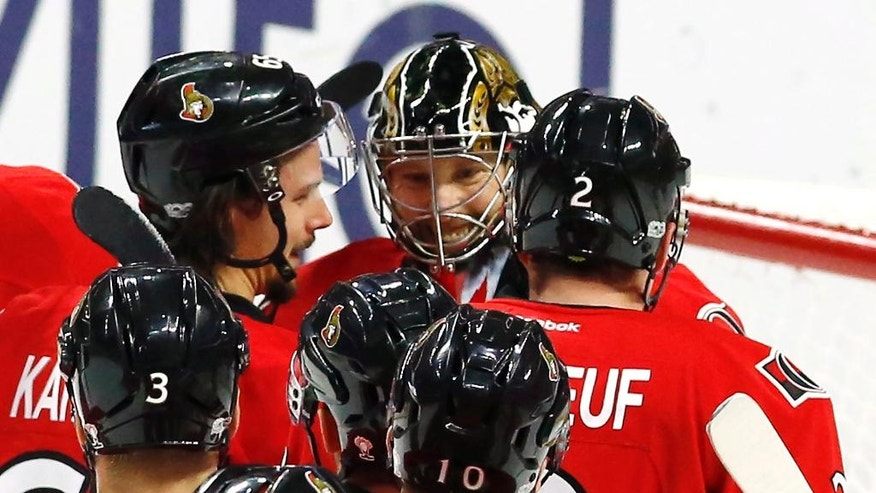 Ottawa Senators goalie Craig Anderson, top center, celebrates with teammates after shutting out the New York Islanders 3-0 in an NHL hockey game in Ottawa, Saturday Feb. 11, 2017. (Fred Chartrand/The Canadian Press via AP)