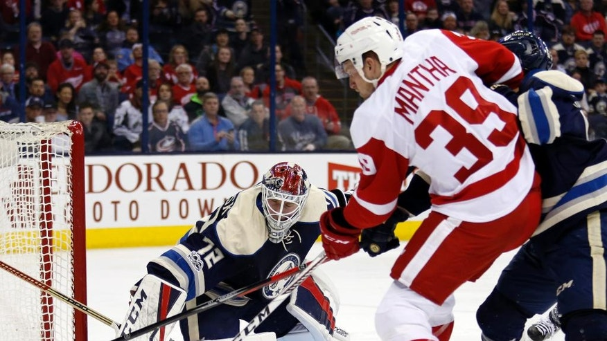 Columbus Blue Jackets goalie Sergei Bobrovsky, left, of Russia, makes a stop against Detroit Red Wings forward Anthony Mantha, center, as Blue Jackets defenseman Markus Nutivaara, of Finland, defends during the first period of an NHL hockey game in Columbus, Ohio, Saturday, Feb. 11, 2017. (AP Photo/Paul Vernon)