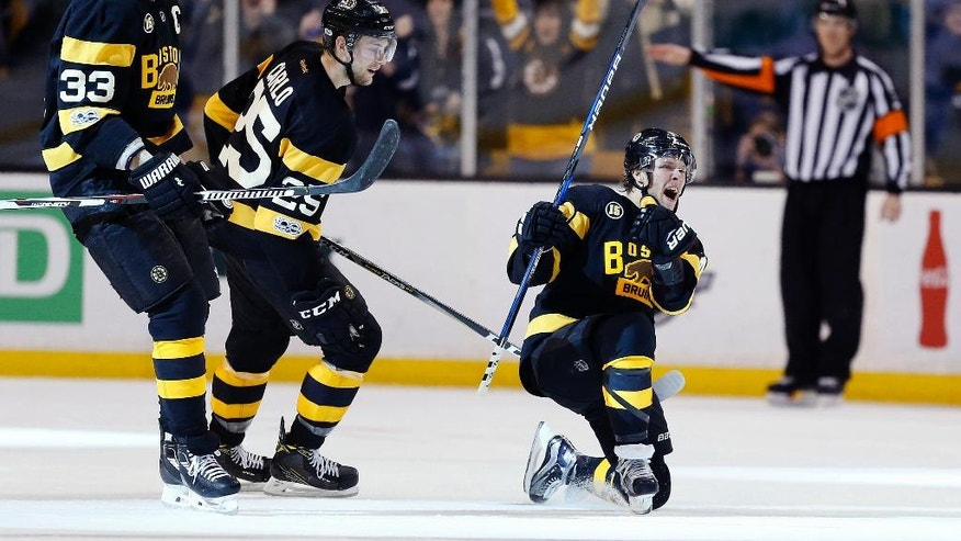 Boston Bruins' David Pastrnak, of the Czech Republic, right, celebrates his goal beside teammates Zdeno Chara (33), of Slovakia, and Brandon Carlo (25) during the third period of an NHL hockey game against the Vancouver Canucks in Boston, Saturday, Feb. 11, 2017. The Bruins won 4-3. (AP Photo/Michael Dwyer)