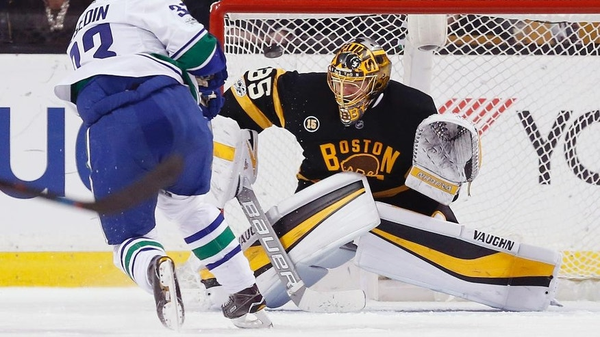 Boston Bruins' Anton Khudobin (35), of Kazakhstan, blocks a shot by Vancouver Canucks' Henrik Sedin (33), of Sweden, during the second period of an NHL hockey game in Boston, Saturday, Feb. 11, 2017. (AP Photo/Michael Dwyer)