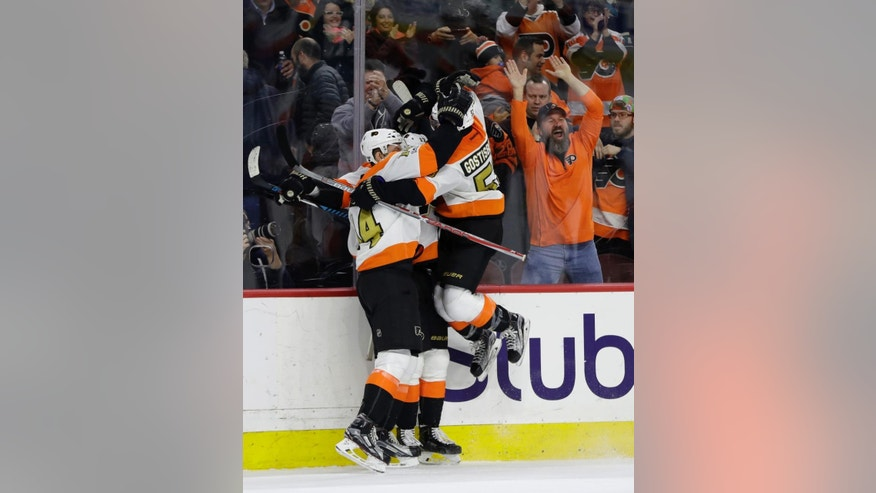 Philadelphia Flyers' Sean Couturier, from left, Wayne Simmonds and Shayne Gostisbehere celebrate after Simmonds' scored the game-winning goal during overtime of an NHL hockey game against the San Jose Sharks, Saturday, Feb. 11, 2017, in Philadelphia. Philadelphia won 2-1. (AP Photo/Matt Slocum)