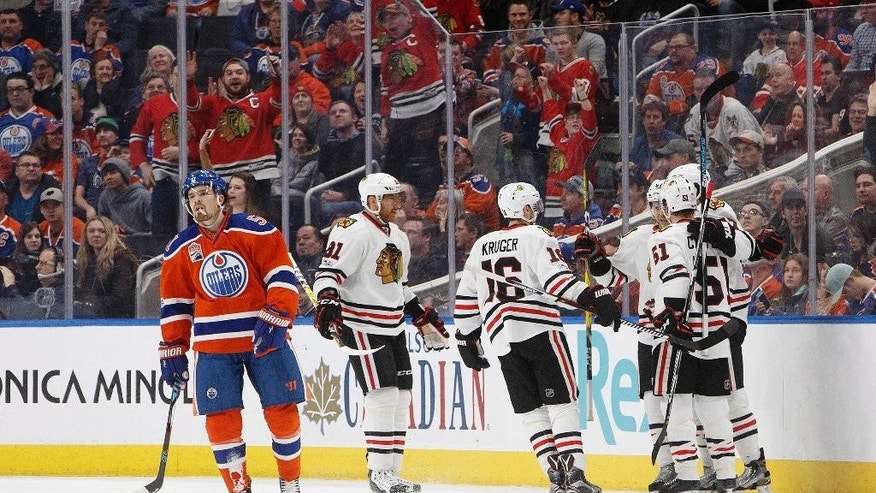 Chicago Blackhawks celebrate a goal as Edmonton Oilers center Anton Lander (51) skates to the bench during the second period of an NHL hockey game Saturday, Feb. 11, 2017, in Edmonton, Alberta. (Jason Franson/The Canadian Press via AP)