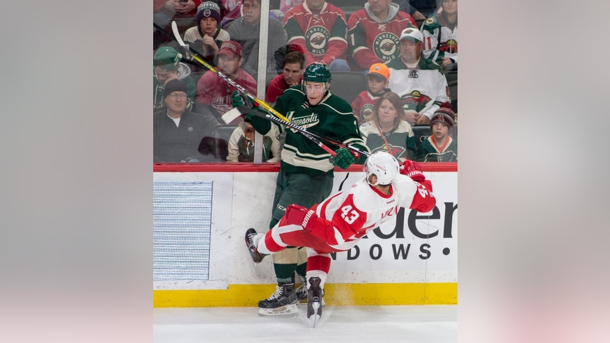 Detroit Red Wings center Darren Helm (43) is upended as he is checked by Minnesota Wild center Charlie Coyle (3) during the first period of an NHL hockey game, Sunday, Feb. 12, 2017, in St. Paul, Minn. (AP Photo/Paul Battaglia)