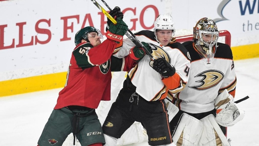 Anaheim Ducks' Cam Fowler, center, pushes Minnesota Wild's Zack Mitchell, left, away from Ducks' goal John Gibson, right in the first period of an NHL hockey game, Tuesday, Feb. 14, 2017, in St. Paul, Minn.(AP Photo/Tom Olmscheid)