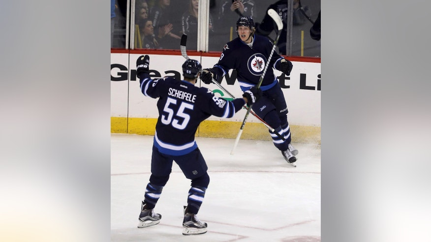 Winnipeg Jets centre Mark Scheifele (55) and right wing Patrik Laine (29) celebrate after Laine scored against the Dallas Stars during first period NHL hockey action in Winnipeg, Manitoba, Tuesday, Feb. 14, 2017. (Trevor Hagan/The Canadian Press via AP)