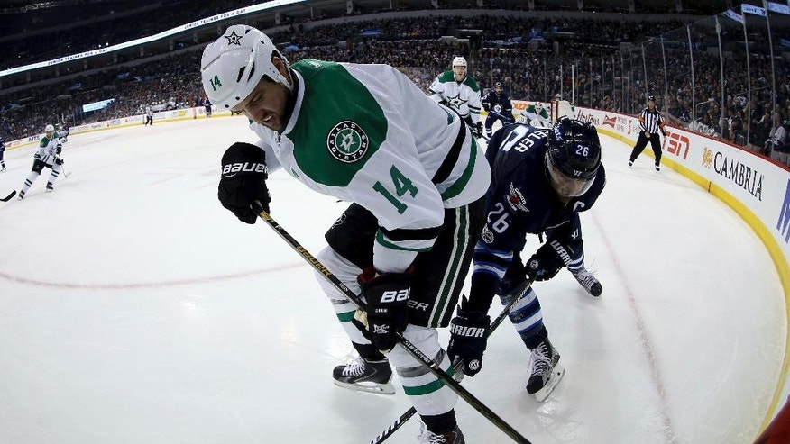 Dallas Stars left wing Jamie Benn (14) and Winnipeg Jets right wing Blake Wheeler (26) battle in the corner during second period NHL hockey action in Winnipeg, Manitoba, Tuesday, Feb. 14, 2017. (Trevor Hagan/The Canadian Press via AP)