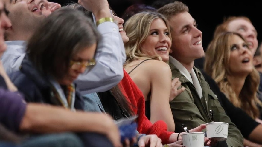 Genie Bouchard, left, poses for photographs with her blind date, John Goehrke, right, during the second half of an NBA basketball game between the Brooklyn Nets and the Milwaukee Bucks Wednesday, Feb. 15, 2017, in New York. After losing a Super Bowl bet on Twitter Bouchard agreed to go on a date with a random fan. (AP Photo/Frank Franklin II)