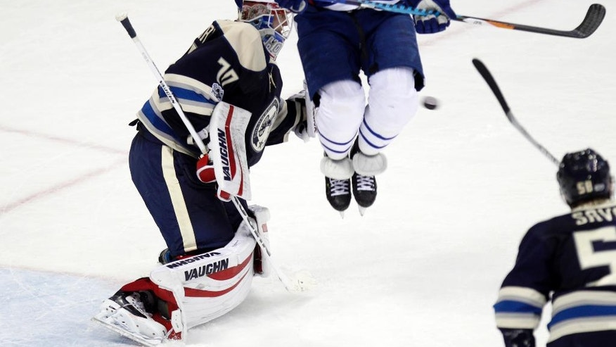 Toronto Maple Leafs forward Leo Komarov, right, of Estonia, tries to jump clear of a shot against Columbus Blue Jackets goalie Joonas Korpisalo, of Finland, during the third period of an NHL hockey game in Columbus, Ohio, Wednesday, Feb. 15, 2017. The Blue Jackets won 5-2. (AP Photo/Paul Vernon)