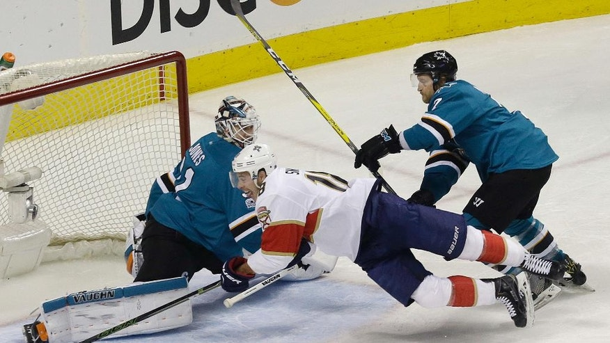 Florida Panthers right wing Reilly Smith, center, attempts a shot between San Jose Sharks goalie Martin Jones, left, and defenseman Paul Martin during the first period of an NHL hockey game in San Jose, Calif., Wednesday, Feb. 15, 2017. (AP Photo/Jeff Chiu)