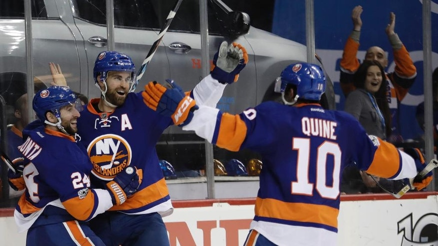 New York Islanders' Andrew Ladd, center, celebrates with teammates Stephen Gionta (24) and Alan Quine (10) after scoring a goal during the second period of an NHL hockey game against the New York Rangers on Thursday, Feb. 16, 2017, in New York. (AP Photo/Frank Franklin II)