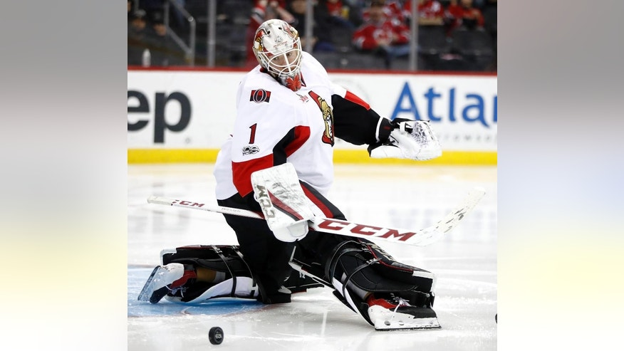 Ottawa Senators goalie Mike Condon looks at the puck after it got by him and hit his post but didn't enter the net during the second period of an NHL hockey game against the New Jersey Devils, Thursday, Feb. 16, 2017, in Newark, N.J. (AP Photo/Julio Cortez)