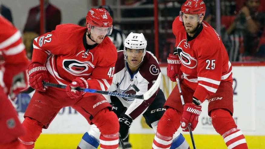 Carolina Hurricanes' Joakim Nordstrom (42), of Sweden, and Viktor Stalberg (25), of Sweden, chase the puck with Colorado Avalanche's Andreas Martinsen (27), of Norway, during the first period of an NHL hockey game in Raleigh, N.C., Friday, Feb. 17, 2017. (AP Photo/Gerry Broome)