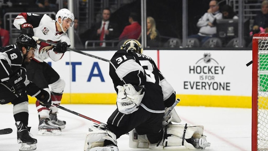 Arizona Coyotes left wing Brendan Perlini, o Britain, center, scores on Los Angeles Kings goalie Peter Budaj, right, of Slovakia, as defenseman Drew Doughty tries to defend during the first period of an NHL hockey game, Thursday, Feb. 16, 2017, in Los Angeles. (AP Photo/Mark J. Terrill)