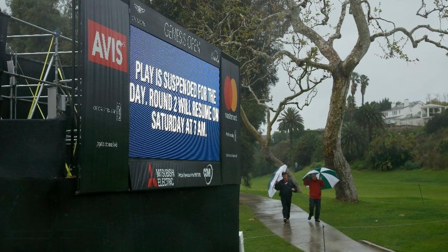 Spectators walk to the clubhouse after play was suspended during the second round of the Genesis Open golf tournament at Riviera Country Club Friday, Feb. 17, 2017, in the Pacific Palisades area of Los Angeles. (AP Photo/Ryan Kang)