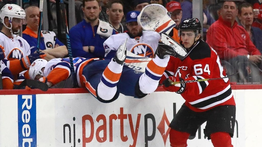 New York Islanders center Casey Cizikas, left, goes over the boards onto his bench while trying to check New Jersey Devils left wing Joseph Blandisi during the second period of an NHL hockey game, Saturday, Feb. 18, 2017, in Newark, N.J. (AP Photo/Julio Cortez)