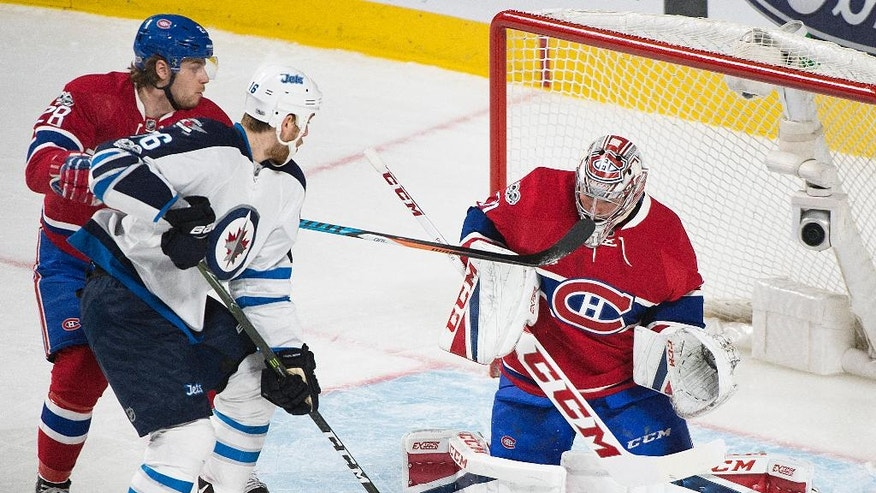 Montreal Canadiens goaltender Carey Price makes a save against Winnipeg Jets' Shawn Matthias (16) as Canadiens' Nathan Beaulieu (28) defends during the first period of an NHL hockey game in Montreal, Saturday, Feb. 18, 2017. (Graham Hughes/The Canadian Press via AP)