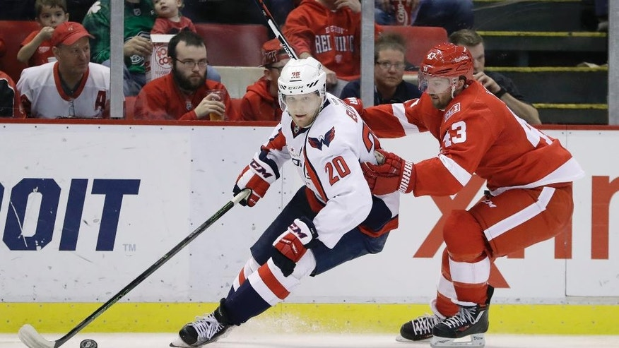 Washington Capitals center Lars Eller (20) controls the puck next to Detroit Red Wings center Darren Helm (43) during the second period of an NHL hockey game, Saturday, Feb. 18, 2017, in Detroit. (AP Photo/Carlos Osorio)