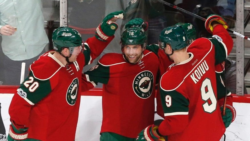 Minnesota Wild's Jason Zucker, center, celebrates his goal off Nashville Predators goalie Pekka Rinne, of Finland, with teammates during the second period of an NHL hockey game, Saturday, Feb. 18, 2017, in St. Paul, Minn. (AP Photo/Jim Mone)