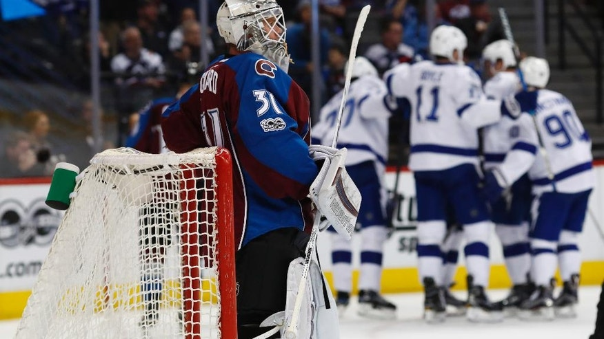 Colorado Avalanche goalie Calvin Pickard, front, reacts as Tampa Bay Lightning center Vladislav Namestnikov celebrates with teammates after scoring a goal in the second period of an NHL hockey game Sunday, Feb. 19, 2017, in Denver. (AP Photo/David Zalubowski)