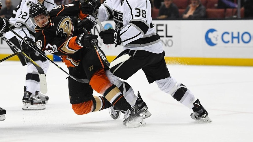Anaheim Ducks center Rickard Rakell, center, of Sweden, shoots the puck as Los Angeles Kings defenseman Paul LaDue, right, defends during the second period of an NHL hockey game, Sunday, Feb. 19, 2017, in Anaheim, Calif. (AP Photo/Mark J. Terrill)