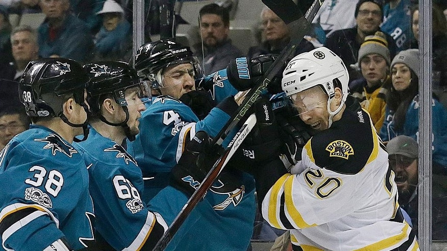 Boston Bruins center Riley Nash (20) and San Jose Sharks defenseman Brenden Dillon (4) shove each other during the second period of an NHL hockey game in San Jose, Calif., Sunday, Feb. 19, 2017. (AP Photo/Jeff Chiu)