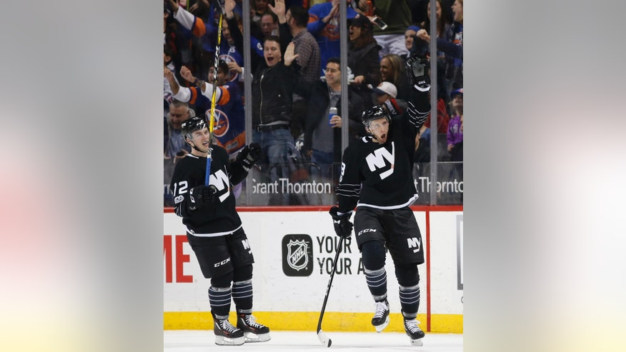 New York Islanders right wing Ryan Strome (18) reacts after scoring a goal during the first period of an NHL hockey game against the New Jersey Devils, Sunday, Feb. 19, 2017, in New York. New York Islanders left wing Anthony Beauvillier (72) joins in the celebration. (AP Photo/Kathy Willens)