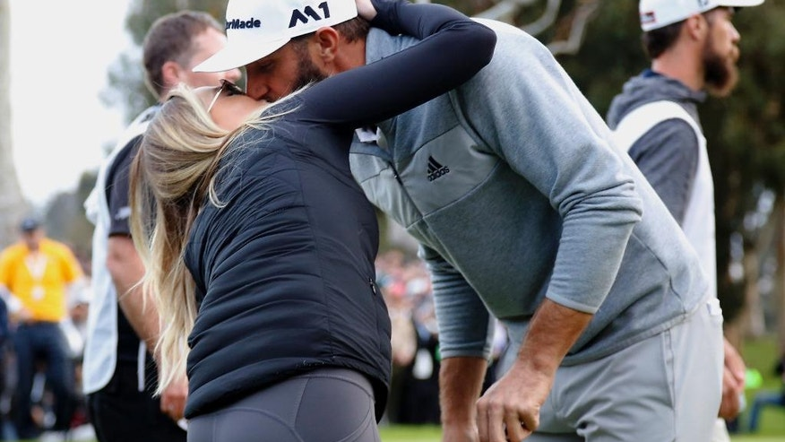 Dustin Johnson kisses his wife Paulina Gretzky on the 18th green after winning the Genesis Open golf tournament at Riviera Country Club on Sunday, Feb. 19, 2017, in the Pacific Palisades area of Los Angeles. (AP Photo/Ryan Kang)