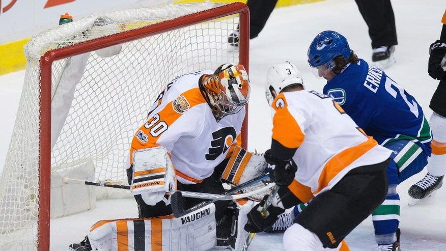 Vancouver Canucks' Loui Eriksson, right, of Sweden, is stopped by Philadelphia Flyers' goalie Michal Neuvirth, of the Czech Republic, as Radko Gudas, of the Czech Republic, defends during the first period of an NHL hockey game in Vancouver, British Columbia, on Sunday, Feb. 19, 2017. (Darryl Dyck/The Canadian Press via AP)