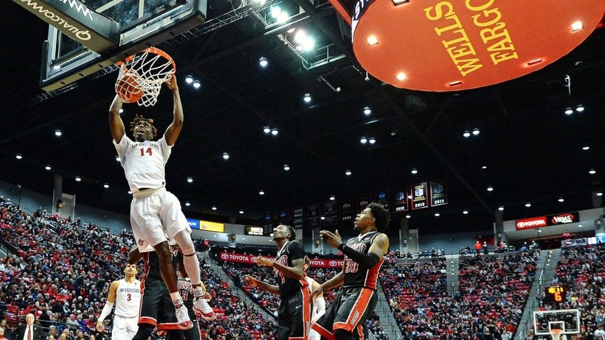 Feb 19, 2017; San Diego, CA, USA; San Diego State Aztecs forward Zylan Cheatham (14) dunks as UNLV Rebels guard Jovan Mooring (30) and guard Kris Clyburn (1) look on during the second half at Viejas Arena at Aztec Bowl. Mandatory Credit: Jake Roth-USA TODAY Sports