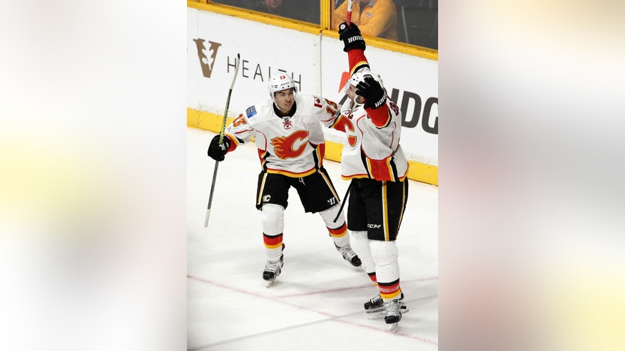 Calgary Flames defenseman Mark Giordano, right, celebrates with Johnny Gaudreau (13) after Giordano scored against the Nashville Predators during overtime in an NHL hockey game Tuesday, Feb. 21, 2017, in Nashville, Tenn. The Flames won6-5. (AP Photo/Mark Humphrey)