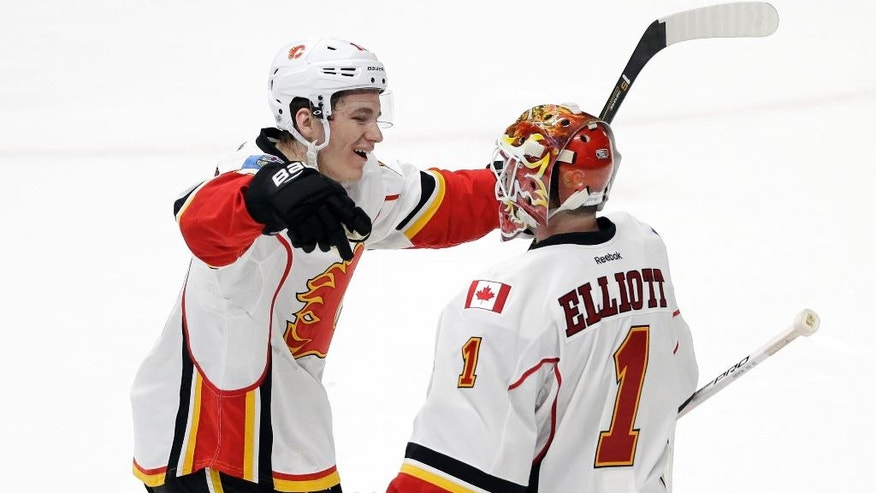 Calgary Flames left wing Matthew Tkachuk, left, celebrates with goalie Brian Elliott (1) after the Flames defeated the Nashville Predators 6-5 in overtime during an NHL hockey game Tuesday, Feb. 21, 2017, in Nashville, Tenn. (AP Photo/Mark Humphrey)