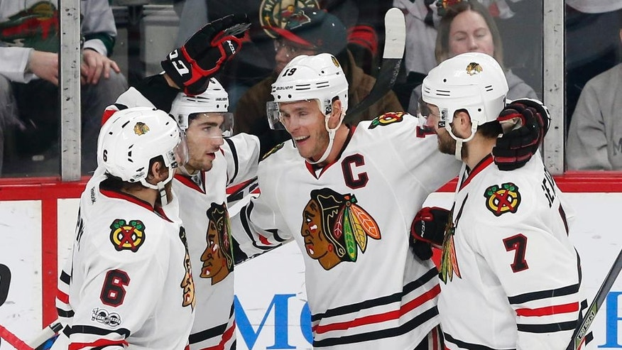 Chicago Blackhawks' Jonathan Toews, second from right, is congratulated on his second goal of the NHL hockey game off Minnesota Wild goalie Devan Dubnyk during the third period of an NHL hockey game, Tuesday, Feb. 21, 2017, in St. Paul, Minn. Toews also scored an empty net goal in the third. The Blackhawks won 5-3. (AP Photo/Jim Mone)
