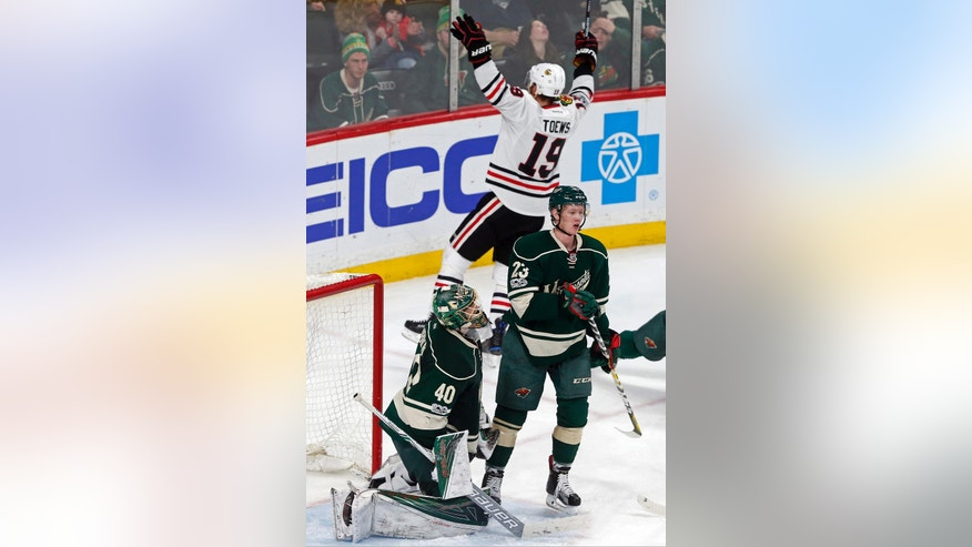 Chicago Blackhawks' Jonathan Toews, top, celebrates his second goal of the NHL hockey game off Minnesota Wild goalie Devan Dubnyk, left, during the third period of an NHL hockey game, Tuesday, Feb. 21, 2017, in St. Paul, Minn. Toews also scored an empty net goal in the third. The Blackhawks won 5-3. (AP Photo/Jim Mone)