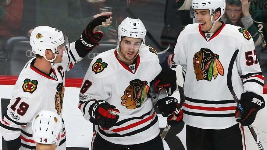 Chicago Blackhawks' Nick Schmaltz, center, is congratulated by Jonathan Toews, left, after his goal off Minnesota Wild goalie Devan Dubnyk during the third period of an NHL hockey game Tuesday, Feb. 21, 2017, in St. Paul, Minn. The Blackhawks won 5-3. Toews scored three goals in the game. (AP Photo/Jim Mone)