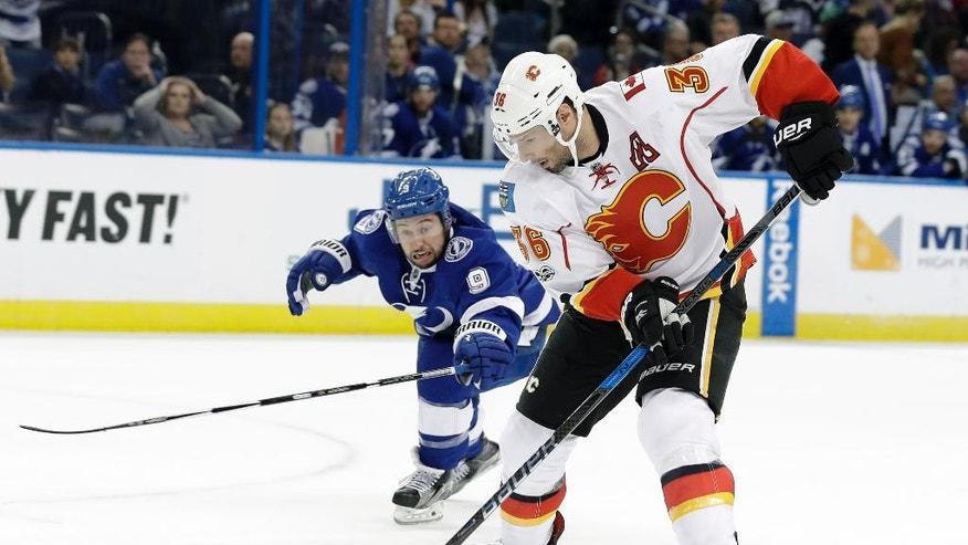 Calgary Flames right wing Troy Brouwer (36) gets around Tampa Bay Lightning center Tyler Johnson during the first period of an NHL hockey game Thursday, Feb. 23, 2017, in Tampa, Fla. (AP Photo/Chris O'Meara)