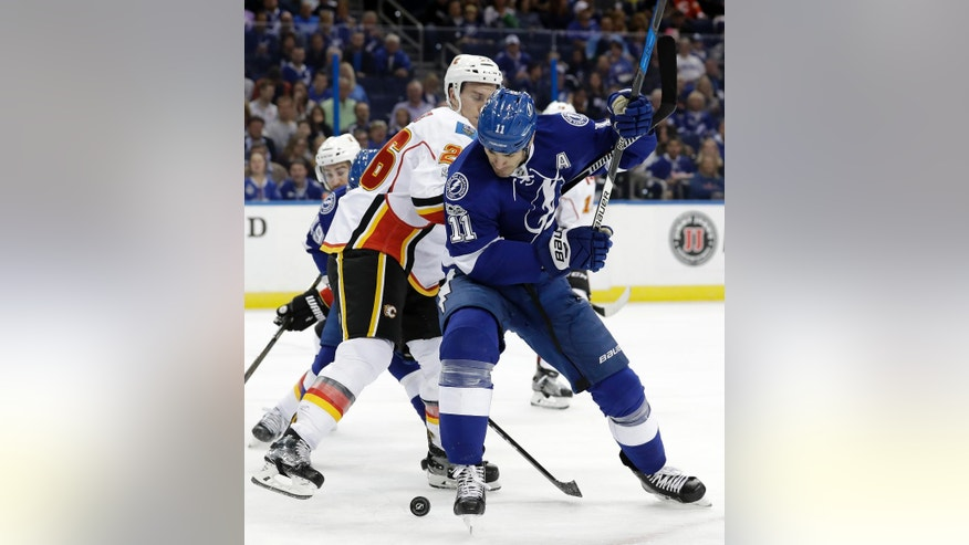 Tampa Bay Lightning center Brian Boyle (11) and Calgary Flames defenseman Michael Stone (26) battle for a loose puck during the second period of an NHL hockey game Thursday, Feb. 23, 2017, in Tampa, Fla. (AP Photo/Chris O'Meara)