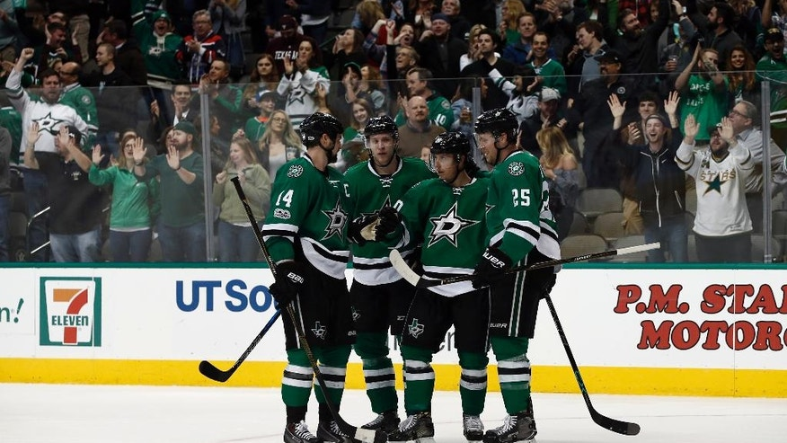 Dallas Stars' Jamie Benn (14), Esa Lindell (23), Cody Eakin (20) and Brett Ritchie (25) celebrate Eakin's goals against the Arizona Coyotes during the third period of an NHL hockey game, Friday, Feb. 24, 2017, in Dallas. (AP Photo/Mike Stone)