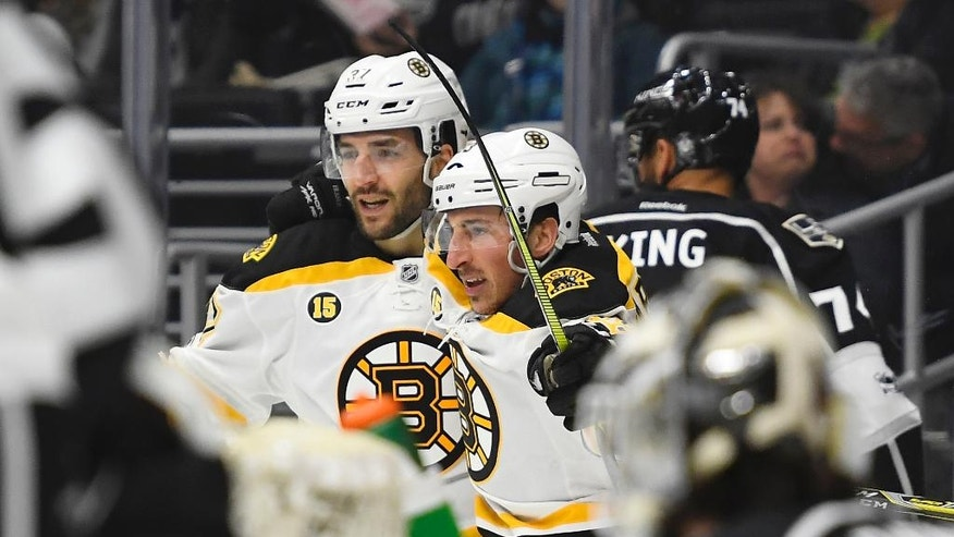 Boston Bruins left wing Brad Marchand, second from left, celebrates his goal with center Patrice Bergeron, left, as Los Angeles Kings goalie Peter Budaj, lower right, of Slovakia, waits during the first period of an NHL hockey game, Thursday, Feb. 23, 2017, in Los Angeles. (AP Photo/Mark J. Terrill)