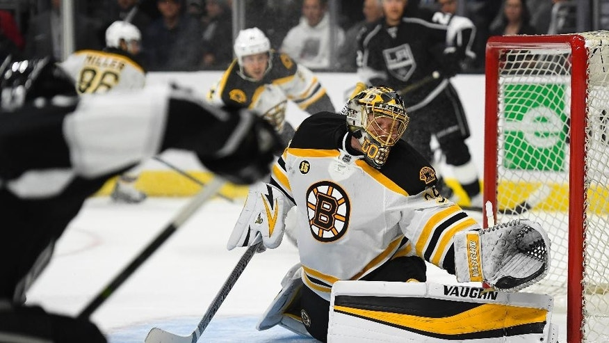 Boston Bruins goalie Anton Khudobin, right, of Kazakhstan, stops a shot by Los Angeles Kings defenseman Kevin Gravel, foreground left, during the second period of an NHL hockey game, Thursday, Feb. 23, 2017, in Los Angeles. (AP Photo/Mark J. Terrill)