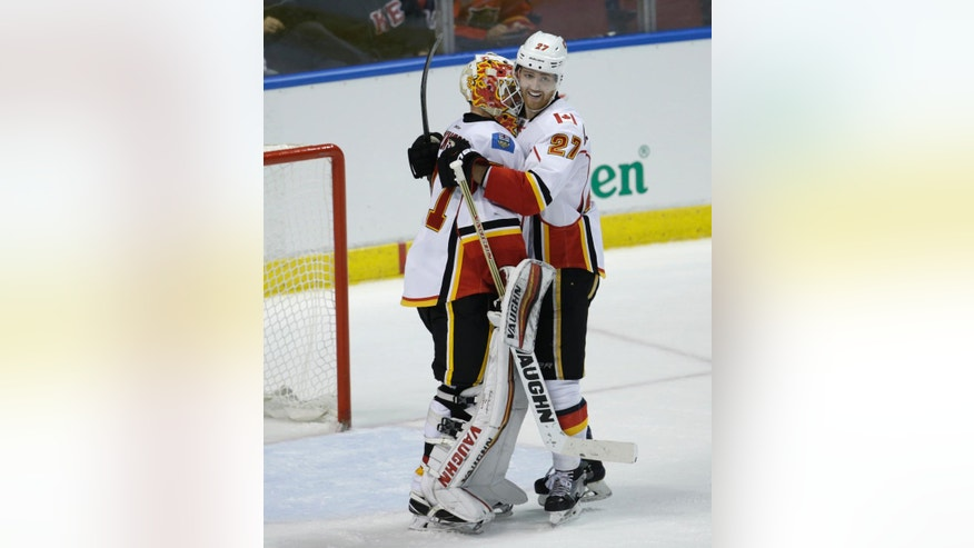 Calgary Flames goalie Chad Johnson, left, is hugged by defenseman Dougie Hamilton (27) after they defeated the Florida Panthers in an NHL hockey game, Friday, Feb. 24, 2017, in Sunrise, Fla. (AP Photo/Lynne Sladky)