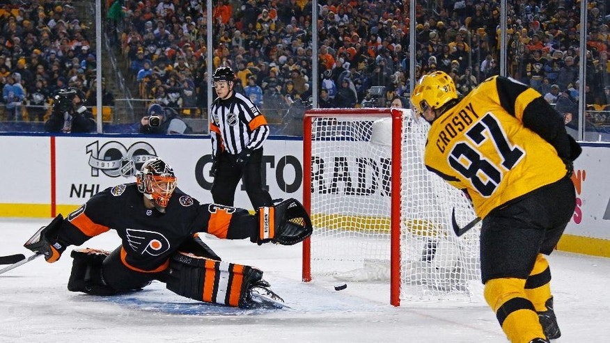 Pittsburgh Penguins' Sidney Crosby (87) gets a shot past Philadelphia Flyers' Michal Neuvirth (30) for a goal during the first period of an NHL Stadium Series hockey game at Heinz Field in Pittsburgh, Saturday, Feb. 25, 2017. (AP Photo/Gene J. Puskar)