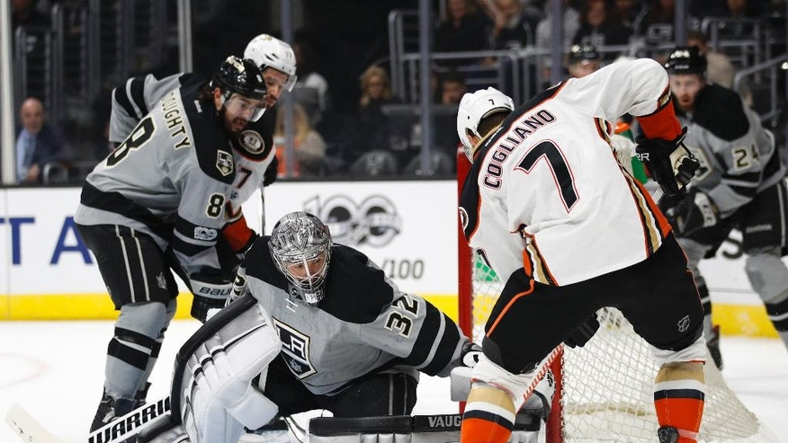 Los Angeles Kings goalie Jonathan Quick, left, makes a save against Anaheim Ducks' Andrew Cogliano during the first period of an NHL hockey game Saturday, Feb. 25, 2017, in Los Angeles.  (AP Photo/Jae C. Hong)