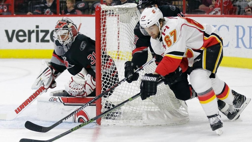 Calgary Flames' Michael Frolik (67), of the Czech Republic, tries to score against Carolina Hurricanes goalie Eddie Lack, of Sweden, during the first period of an NHL hockey game in Raleigh, N.C., Sunday, Feb. 26, 2017. (AP Photo/Gerry Broome)