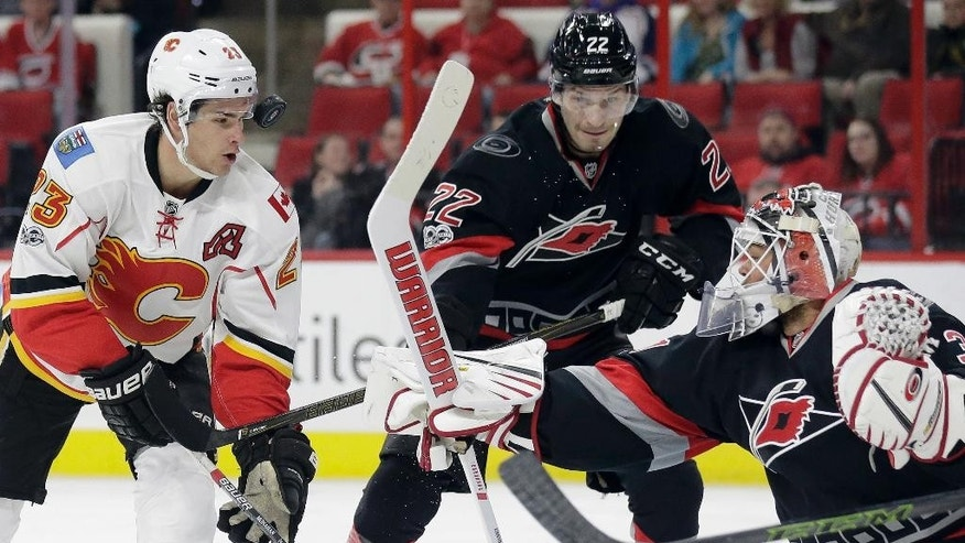 Calgary Flames' Sean Monahan (23) tries to score against Carolina Hurricanes goalie Eddie Lack, of Sweden, as Hurricanes Brett Pesce (22) watches during the first period of an NHL hockey game in Raleigh, N.C., Sunday, Feb. 26, 2017. (AP Photo/Gerry Broome)