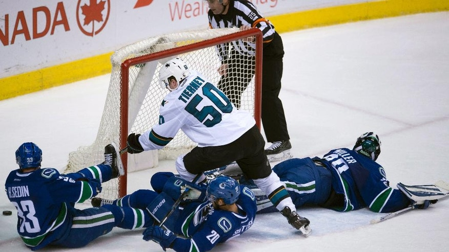 San Jose Sharks center Chris Tierney (50) fails to get a shot past Vancouver Canucks goalie Ryan Miller (30) as Canucks center Henrik Sedin (33) and center Brandon Sutter (20) watch during the second period of an NHL hockey game Saturday, Feb. 25, 2017, in Vancouver, British Columbia. (Jonathan Hayward/The Canadian Press via AP)