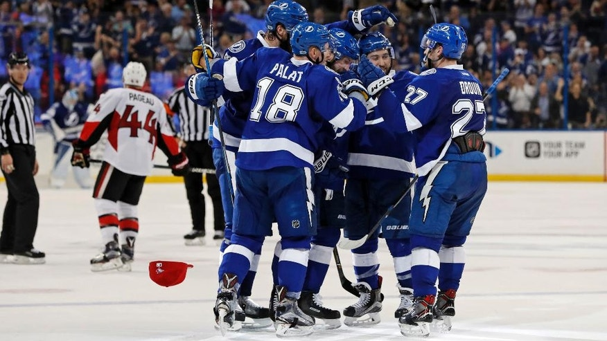 Members of the Tampa Bay Lightning, including Ondrej Palat (18), of the Czech Republic, and Jonathan Drouin (27) congratulate Nikita Kucherov, center, of Russia, on his third goal of the second period of an NHL hockey game against the Ottawa Senators on Monday, Feb. 27, 2017, in Tampa, Fla. (AP Photo/Mike Carlson)